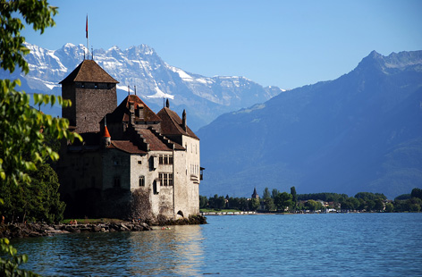 A castle on Lake Geneva with the Alps above.